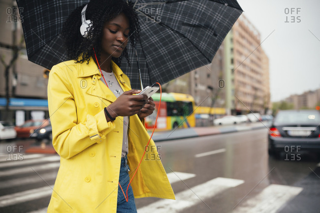 Low angle view of young woman looking down at smartphone while crossing the street on gloomy day