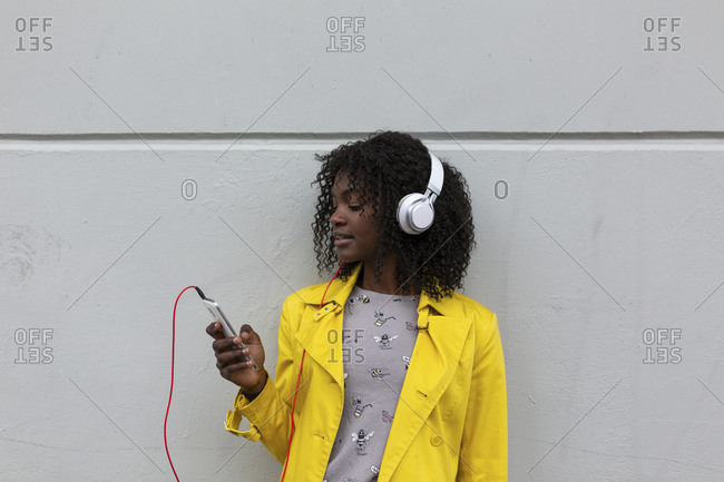 Profile view of young woman standing against wall checking phone