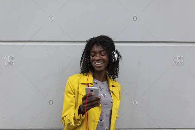 Young black woman standing against wall laughing while checking messages on phone