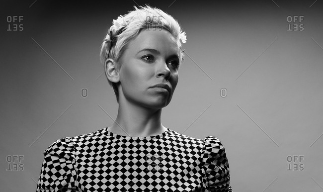 Black and white portrait of attractive blond-haired Caucasian woman in checked  blouse looking aside thoughtfully