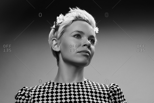 Black and white portrait of elegant blond Caucasian woman in checked dress looking into the distance, low angle view
