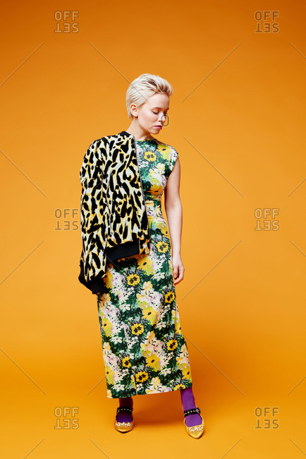 Full-length portrait young blond Caucasian woman demonstrating stylish apparel on orange background