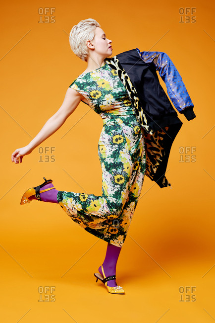 Model demonstrating fashionable look. Portrait of blond-haired Caucasian woman in stylish apparel posing on camera against orange background