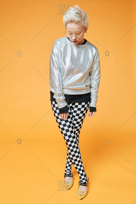 Portrait of blond Caucasian woman in stylish silver sweatshirt and checked pants posing on camera against orange background