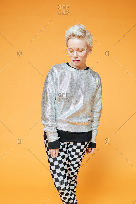 Portrait of young Caucasian pretty woman with short haircut demonstrating casual fashionable look on orange background