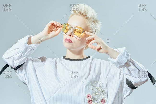 Portrait of beautiful blond-haired woman in loose blouse demonstrating several trendy sunglasses on white background