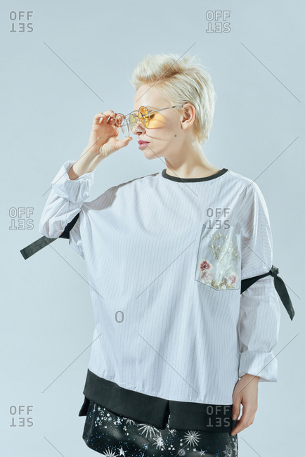 Portrait of attractive blond Caucasian woman in fashionable loose blouse and sunglasses posing on white wall background