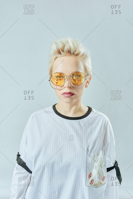 Portrait of attractive Caucasian woman with short spiky hairstyle in trendy sunglasses looking at camera on white background