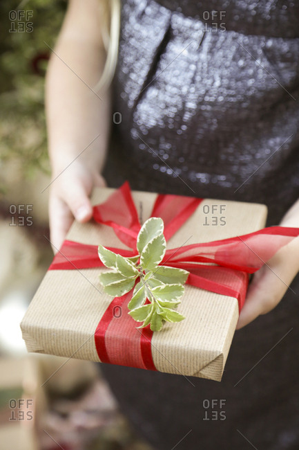 Child holding a wrapped Christmas present with ribbon and sprig of leaves