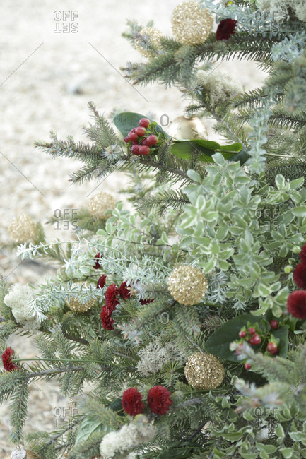 Christmas tree adorned with flowers, berries, and glass ball ornaments
