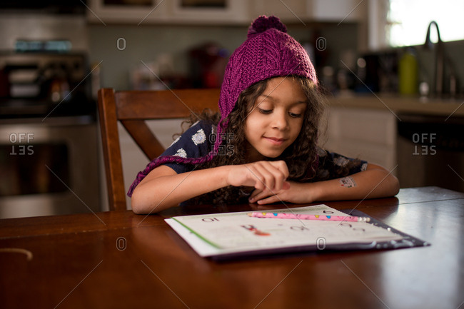 Little girl sitting at table doing homework