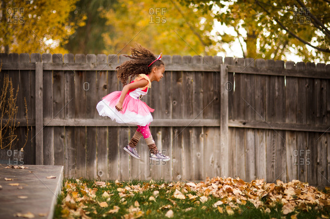 Little girl jumping from backyard deck