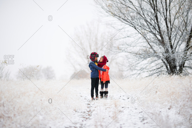 Two kids hugging in the snow
