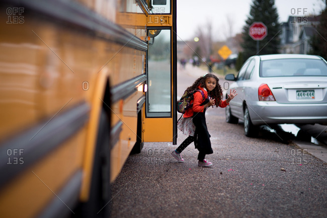 Little girl getting off the school bus