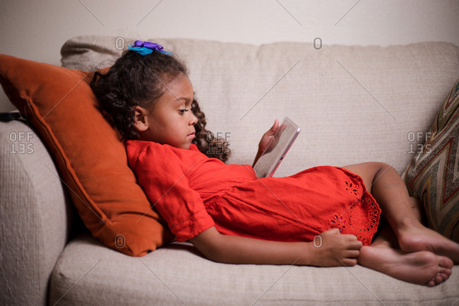 Little girl lying on comfy chair watching videos on tablet