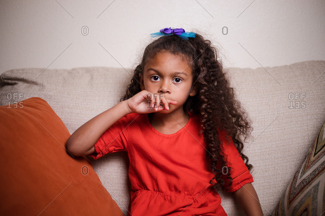 Portrait of a biracial girl sitting in a comfy chair