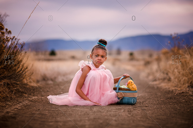 Pretty little girl sitting with Easter basket