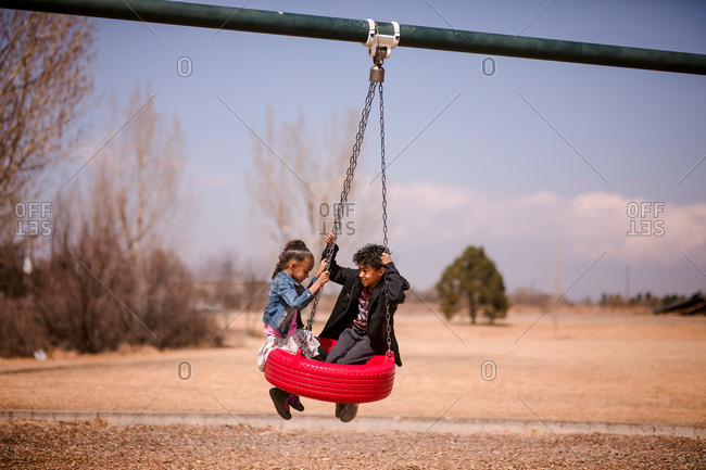 Two kids swinging on a red tire swing