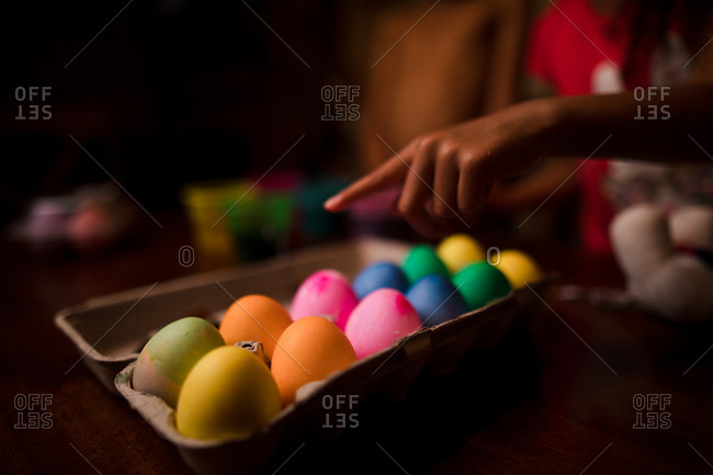 Child pointing to freshly dyed Easter eggs