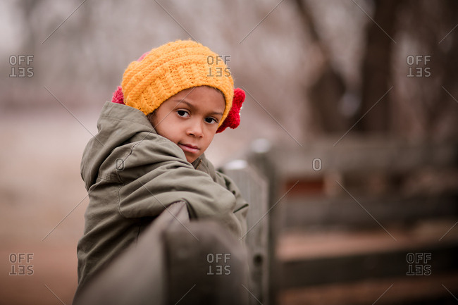 Portrait of a little girl wearing a yellow knit hat