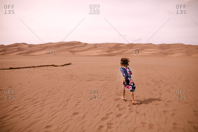 Rear view of a little girl walking in sand