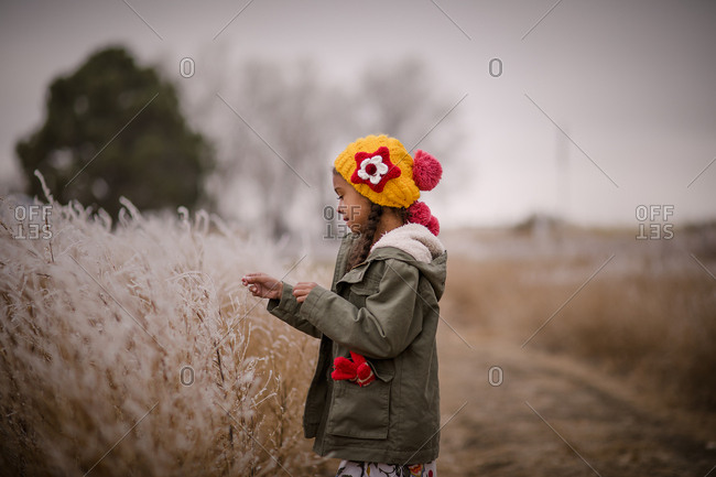 Little girl wearing a yellow knit hat in a rural field