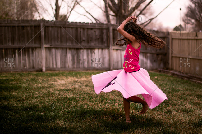 Girl wearing pink skirt twirling in her backyard