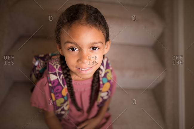Portrait of a biracial girl sitting on steps