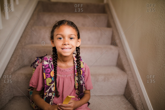 Portrait of a little girl with braids sitting on steps