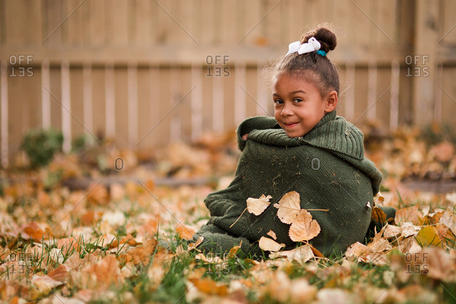 Little girl sitting on ground covered in fallen leaves