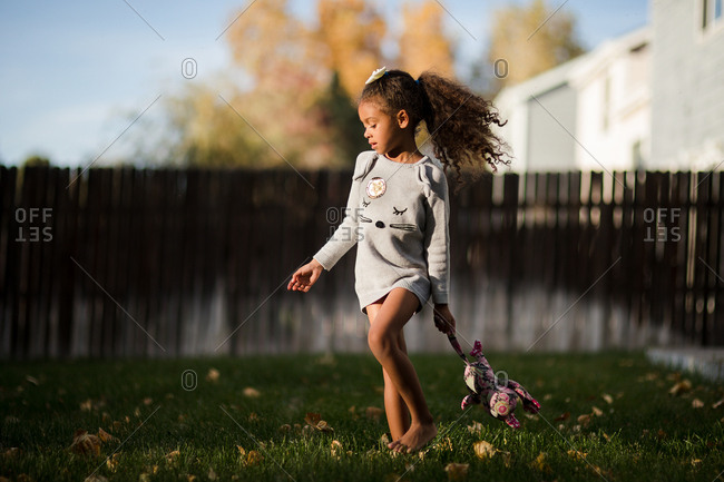 Girl walking in backyard carrying stuffed animal