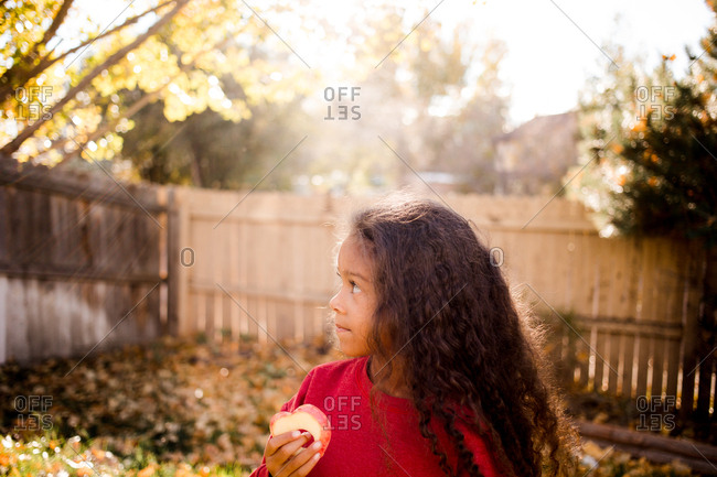 Side view of girl eating an apple outdoors in fall