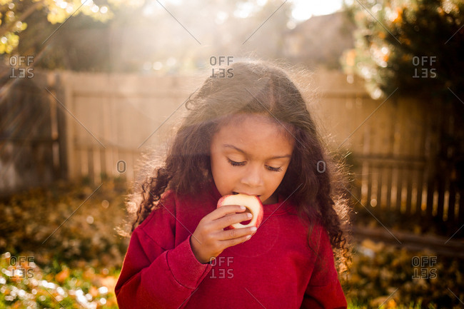 Little girl eating an apple outdoors in fall