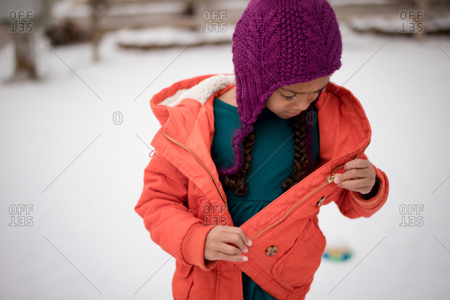 Girl looking at zipper on her jacket outdoors in winter