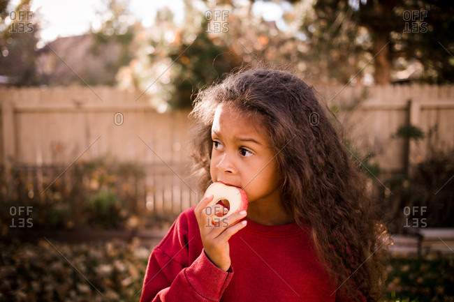 Young girl eating an apple outdoors in fall