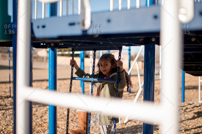 Little girl climbing on playground ladder