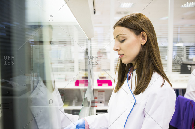 Young woman in laboratory working with material behind safety screen