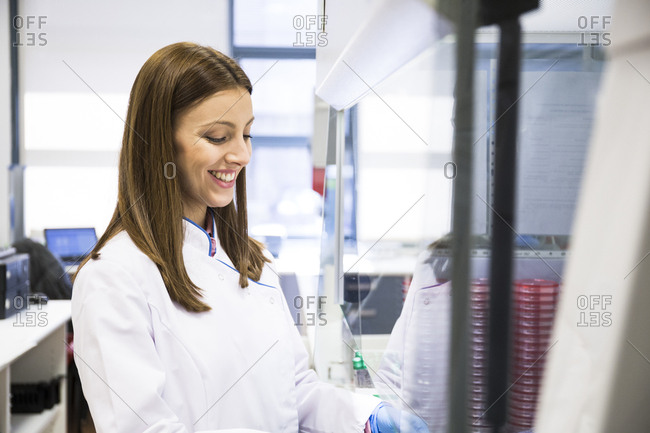 Young female scientist smiling while working with material behind safety screen in laboratory
