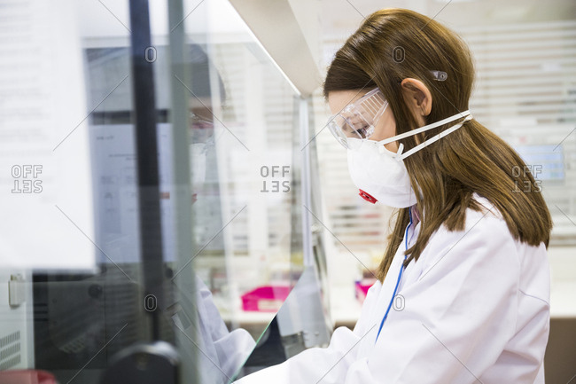 Side view of young woman working in laboratory wearing safety glasses and face mask