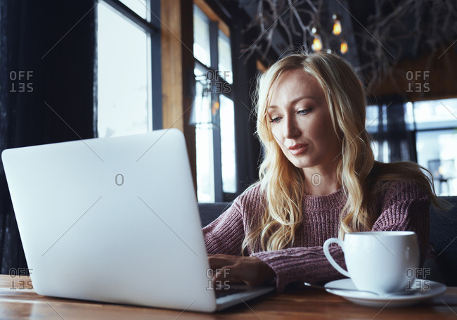 Female life coach blogger using laptop in a coffee shop