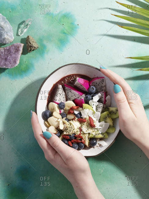 Hands holding dragon fruit dish in magic tropical themed styling