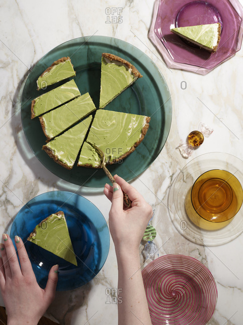 Top view of someone portioning lime pie among festive translucent dishware