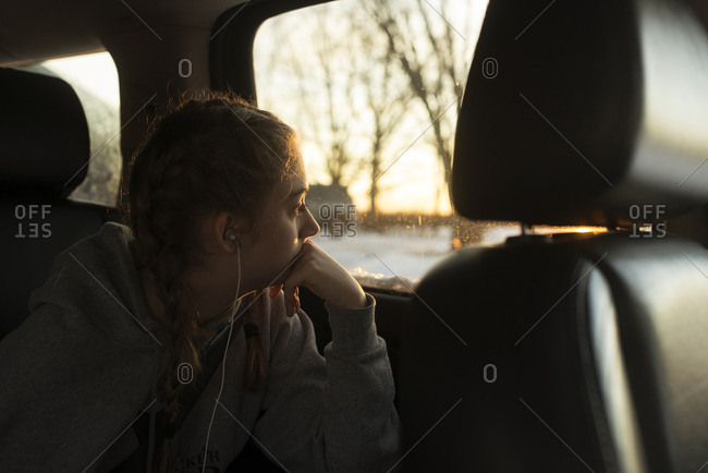 Girl staring out car window listening to headphones