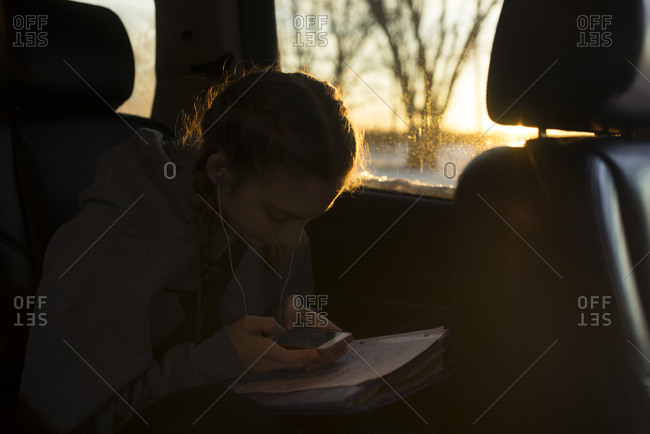 Teenage girl looking at smartphone in car over pile of homework