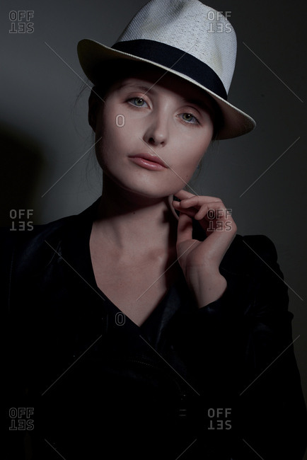 Portrait of a woman touching her chin and wearing a hat