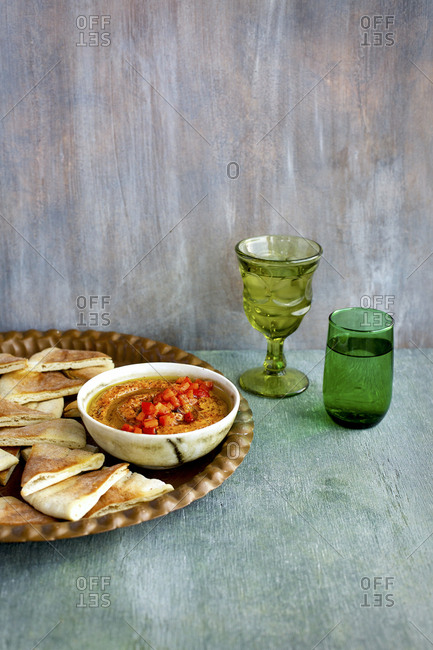 Homemade pita chips served with roasted red pepper harissa pesto and water glasses
