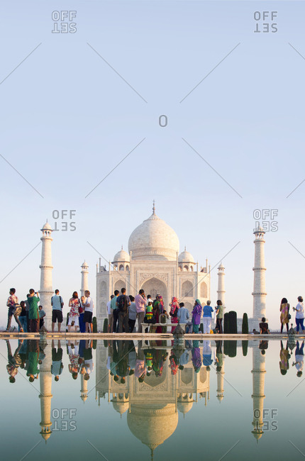 Agra, India - October 9, 2013: Taj Mahal and tourists reflected in pond at morning light
