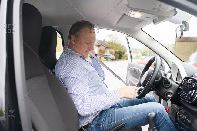 Man putting on seatbelt in parked car