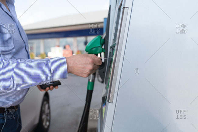 Man paying for gas at outdoor pump with card