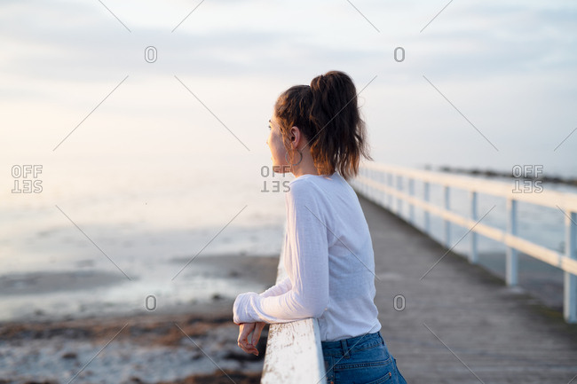 Young woman leaning on pier watching sunrise